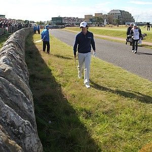 First-round leader Rory McIlroy found his ball nestled near a stone wall at the 17th.