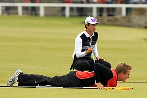 Jin Jeong, rear, lines up his putt on the first green as the Robert Rock's caddie, Jamie Lane, lies on the green.