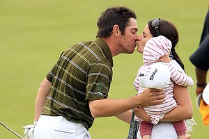 Louis Oosthuizen celebrates on the 18th green with his wife and baby after winning the British Open.