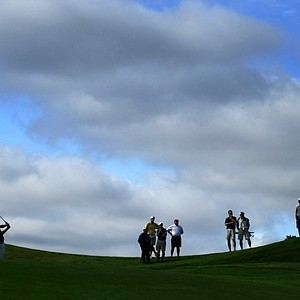 Andrew Fogg, left, of Indiana hits a shot at No. 9 on Monday as spectators watch from the hills.