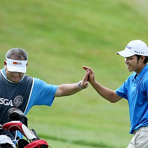 Marcel Puyat of the Philippines high fives his caddie, Anthony Lopez after his second shot at No. 9. Puyat posted a 69 in Monday's round.