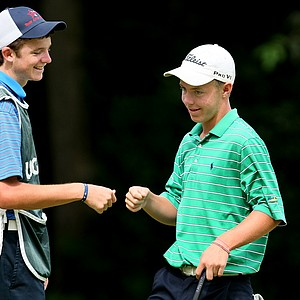 Branson Davis of Mckinney, TX, fist bumps with his caddie Derek Oland, left, after making birdie at No. 7.