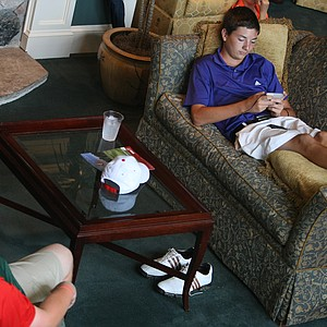Zachary Wright takes a break during the rain delay with his caddie, Adam Lange, left, during Thursday's match play of the 63rd U. S. Junior Amateur Championship.