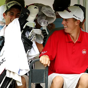 Justin Thomas, right, and his caddie hold on while riding on the back of a cart after winning their match, 2 and 1.