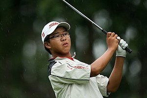 Jim Liu hits his tee shot at No. 6 in the rain.