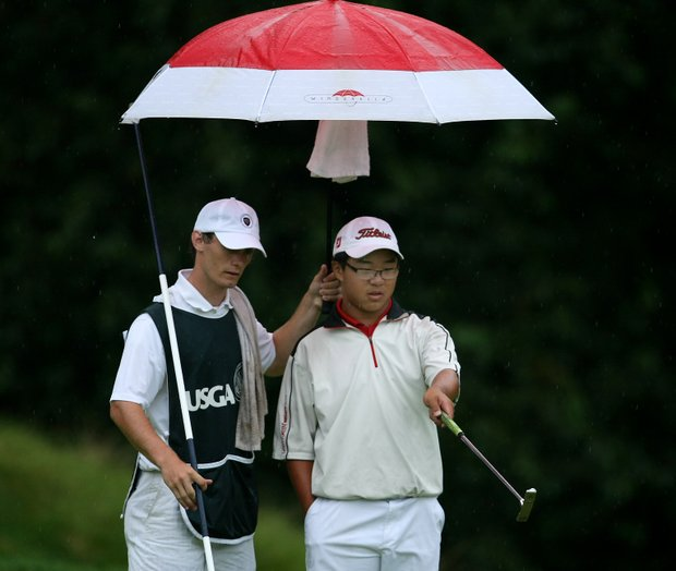 Jim Liu with his caddie Branden Miklosovic at No. 9 during the rain soaked morning.