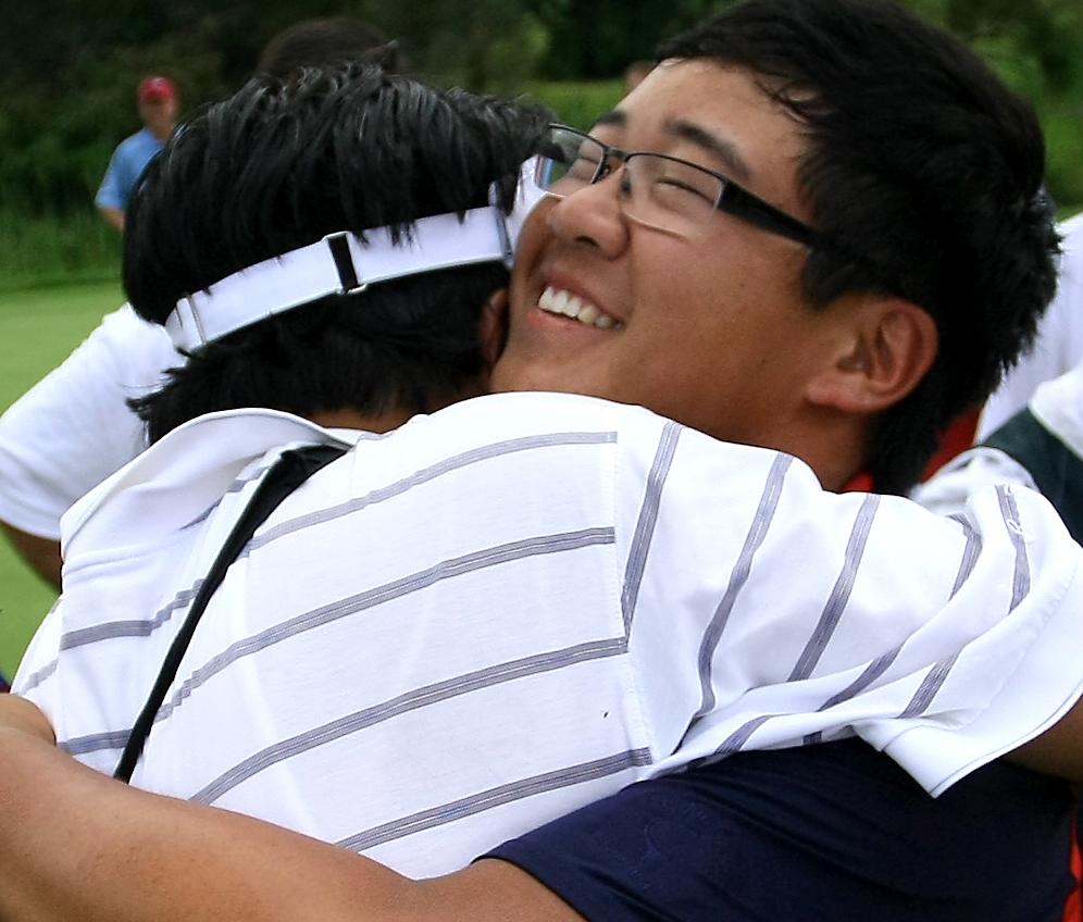 Fourteen-year-old Jim Liu hugs father Yiming Liu after winning the U.S. Junior on Saturday.