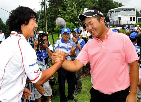Shunsuke Sonoda (right) of Japan is congratulated by former high school teammate Ryo Ishikawa after winning the Mizuno Open on June 27, 2010 in Nishinomiya, Japan.