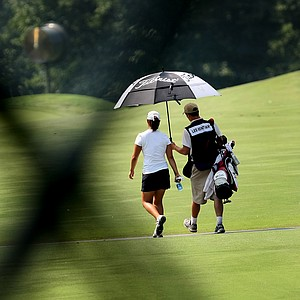 Rebecca Lee-Bentham and her caddie are seen walking down the first fairway through the legs of a TV tower during Monday stroke play.