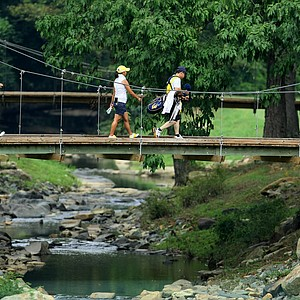 Players walk across a bridge to No. 12 at Charlotte Country Club.