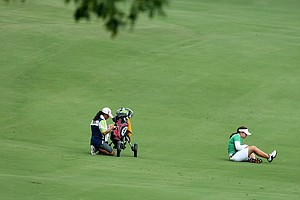 Ariya Jutanugarn and her caddie sit on the 8th fairway waiting to hit their second shot during Monday stroke play.