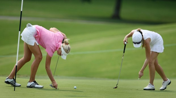 Jessica Korda, left, and Sydnee Michaels, right, repair ball marks at No. 9.