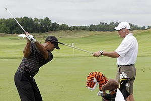 Caddie Steve Williams holds a club as Tiger Woods hits on the driving range during a practice round for the PGA Championship.