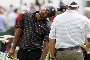 Tiger Woods stretches as he talks to caddie Steve Williams at the range during a practice round for the PGA Championship.