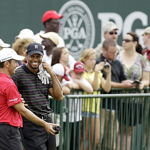 Tiger Woods talks to Mike Weir at the range during a practice round for the PGA Championship.