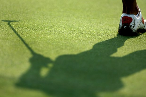 A player's shadow at No. 18 as she putts during Tuesday stroke play.