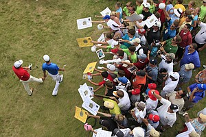 Phil Mickelson, left, and Dustin Johnson make their way to the 17th hole as fans try to get an autographs during a practice round for the PGA Championship.