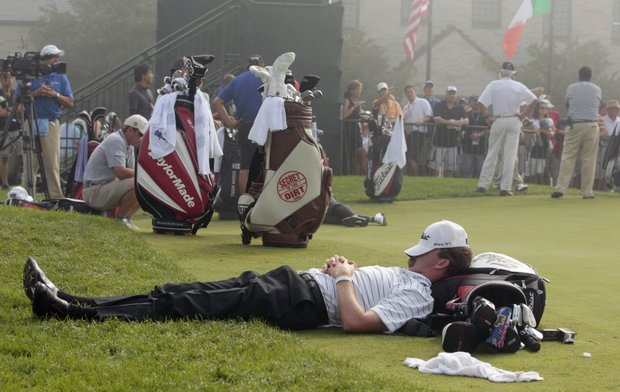 D.J. Trahan rests by the putting green during a fog delay before the first round of the PGA Championship.