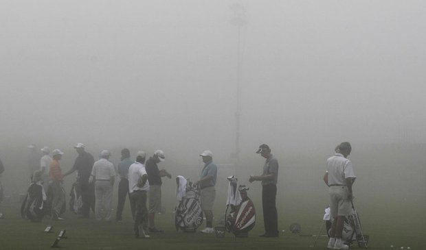 Players line up on the range during a fog delay.