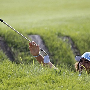 Rickie Fowler hands his caddie his club from a bunker during the first round of the PGA Championship.