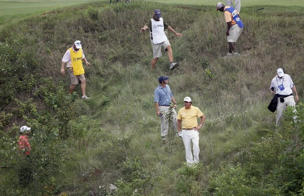 Phil Mickelson gets help looking for his ball in the rough on the 18th hole during the second round of the PGA Championship.