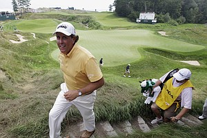 Phil Mickelson makes his way up some stairs on the 18th hole after his first round of the PGA Championship.