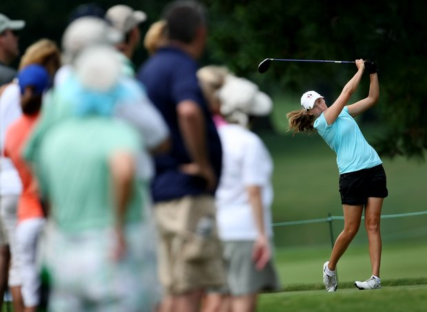 Stephanie Sherlock tees off under the watchful eyes of a crowd at No. 14.