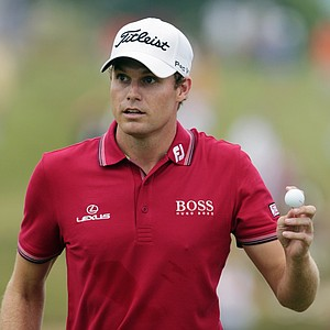 Nick Watney holds up his ball after making a birdie putt on the second hole during the third round of the PGA Championship.