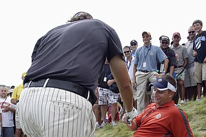 Phil Mickelson hands Matt Reinhart an autographed glove after his ball landed in the fan's lap at the 11th hole during the third round of the PGA Championship.