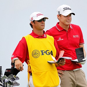 Nick Watney chats with his caddie Chad Reynolds on the third tee during the third round of the 92nd PGA Championship.