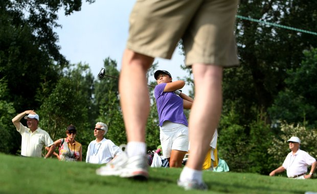 Danielle Kang is framed by a spectators legs as she hits her tee shot at No. 7 during the first 18 holes.