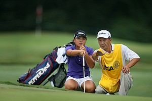 Danielle Kang reads a putt with her father/caddie K.S. Kang during the first 18 holes of Sunday's finals.