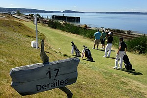 Players wait at the par-3 17th at Chambers Bay.