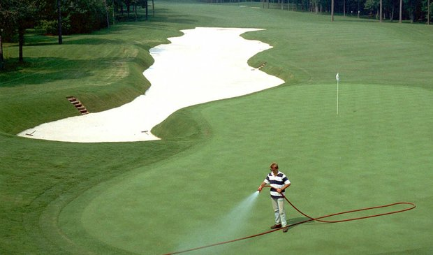 A greenskeeper cools down the greens prior to the 1990 PGA Championship at Shoal Creek.