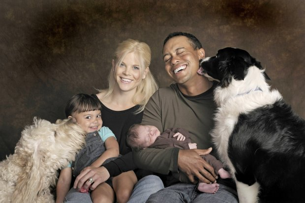 This Feb. 17, 2009, photo provided by the Tiger Woods family shows, Sam, Elin, Tiger and Charlie Woods, from left, and their dogs Yogi, left, and Taz posing in Orlando, Fla.