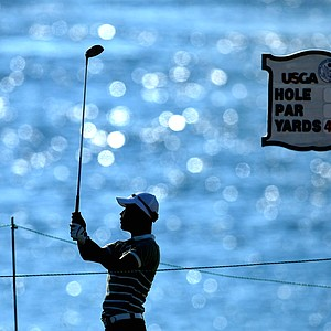 Woo Kim is silhouetted by the Pugent Sound as he hits his tee shot at No. 16.