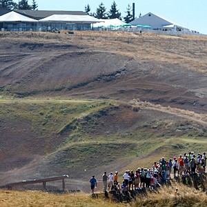 Spectators line up to watch golfers at No. 6 green during the Round of 64. Chambers Bay clubhouse at the top in the background.