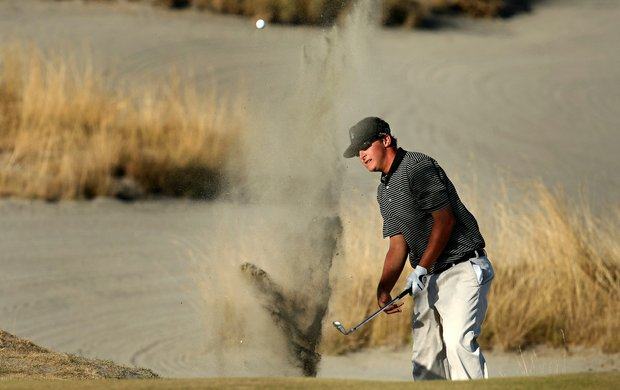 Nick Mullhaupt blasts out of a bunker at Chambers Bay.