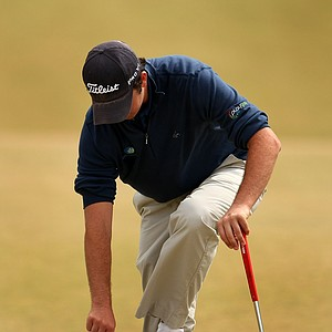 Ryan McCarthy puts his shoes back on at No. 14 after emptying out sand during the Round of 32.