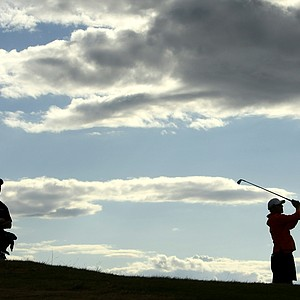 Alex Ching and his caddie at left wait as Morgan Hoffmann hits his drive at No. 12 during the Round of 16.