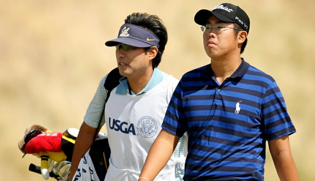Byeong-Hun An walks with his caddie during the Round of 32 at the U.S. Amateur.