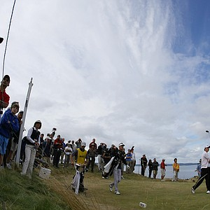 Patrick Cantlay hits his tee shot at No. 12 with spectators behind.