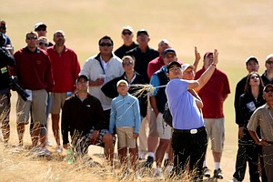 A crowd forms behind Byeong-Hun An as he hits out of fescue at Chambers Bay.