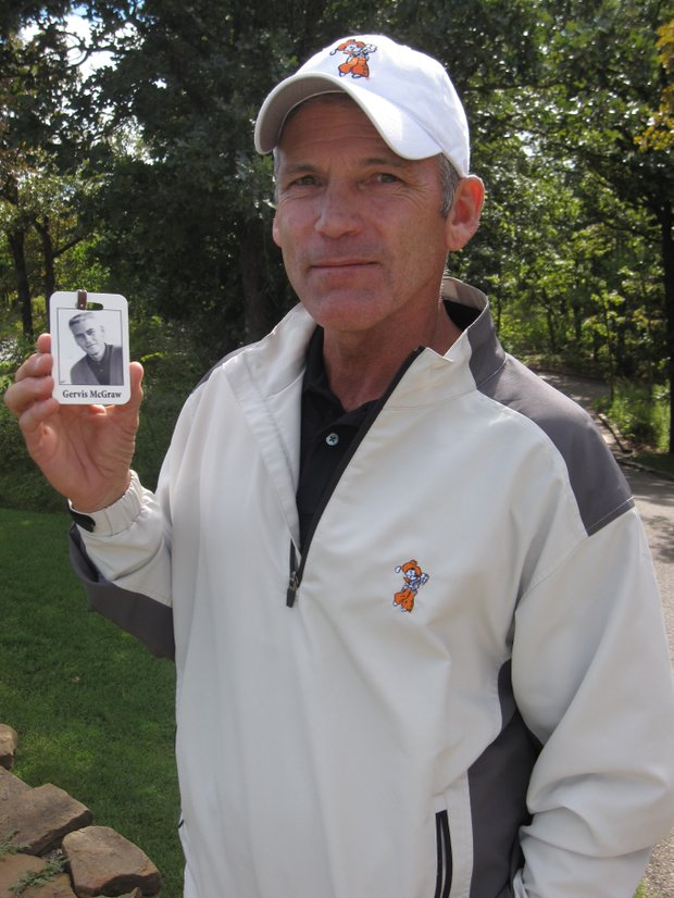 Oklahoma State coach Mike McGraw with the bag tag showing the picture of his father, Gervis.