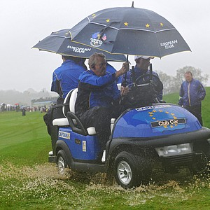 European Ryder Cup captain Colin Montgomerie leaves the third hole on a cart after play was suspended due to heavy rain.