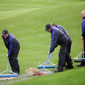 Ground staff clear rain water from the fourth green during the opening four-ball matches.