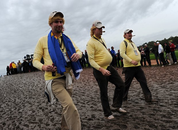 Golf fans dressed as Miguel Angel Jimenez are pictured walking through the mud following heavy rainfall on the second day of the 2010 Ryder Cup.