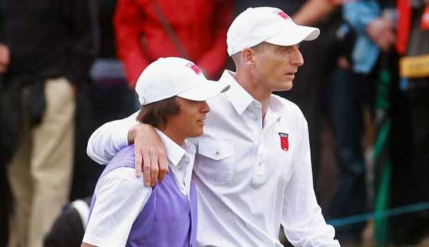 Jim Furyk consoles Rickie Fowler after Fowler dropped the wrong kind of ball in their foursomes match, causing the duo to lose the hole.