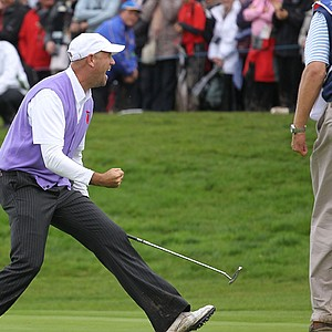 Stewart Cink celebrates a birdie putt on the 17th green alongside caddie Lance Bennett during the rescheduled afternoon foursomes matches during the 2010 Ryder Cup.