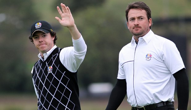 Rory McIlroy (left) waves to the crowd with teammate Graeme McDowell during the Sunday morning foursomes matches.